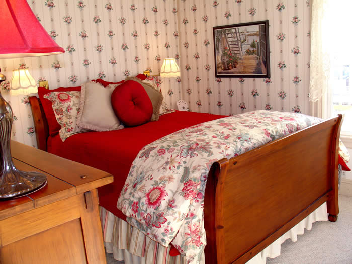 The Abbott guest room has a Queen Sleigh bed with bold red and floral bedding