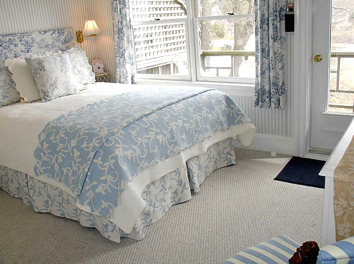 The Hawthorne, a queen room with private balcony and harbor view has blue and white bedding and matching Toile curtains on windows that overlook the private deck with views to the harbor at Kingsleigh Inn