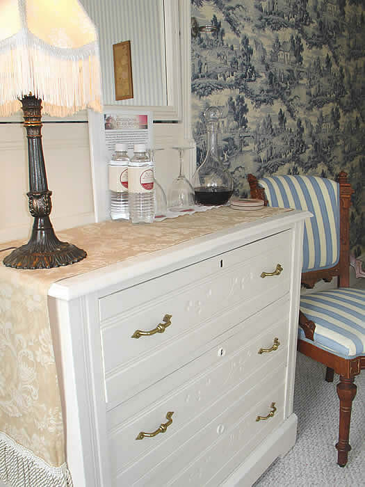 The Hawthorne has an antique white dresser, blue and white stripped chair and toile wallpaper which matches curtains