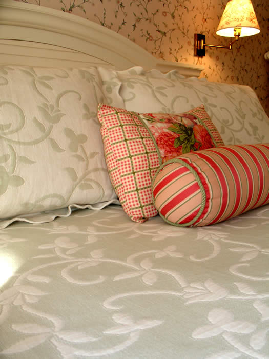 The Victoria, a kiing bed guestroom on the 2nd floor with cream, sage and delicate floral wallpaper and bed skirts