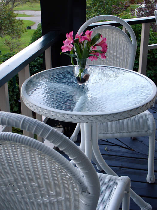 A White Wicker Bistro table for 2 on our outdoor Covered Breakfast Deck