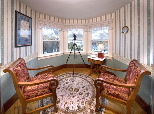 The Turret room in the suite overlooks the beautiful harbor and has 2 comfy chairs access to a Private Deck with a wonderful view of the Harbor and a Telescope!